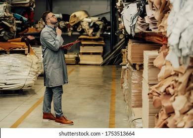 Der Manager führt eine Bestandsaufnahme des Leder und der Leder, die in der Fabrik fehlen.Manager in einer Lederschuhfabrik