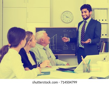 Manager male is reading financial report to colleagues on meeting in the office.