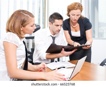 Manager man listening to his red-haired office worker and looking at certain documents during meeting in board room. People communicating about future business projects.