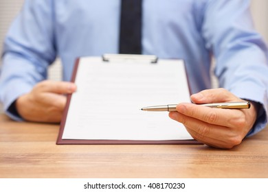 manager is offering a pen to sign a document or agreement