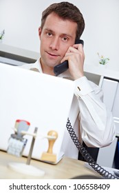 Manager in office making a phone call at his desk