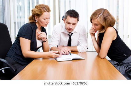 Manager with office workers on meeting in board room