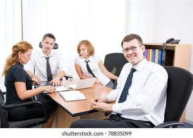 Manager on meeting with office workers in board room