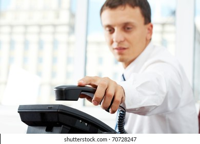 A manager picking up telephone receiver
