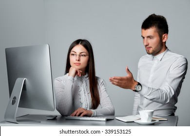 Manager pointing at something to his secretary on a computer in an office isolated on grey background.