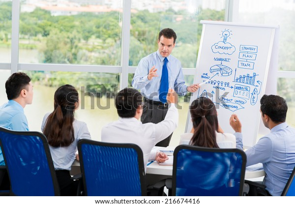 Manager presenting new business strategy to his employees