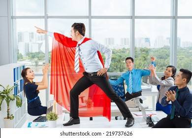 Manager in a red cape posing in front of his colleagues