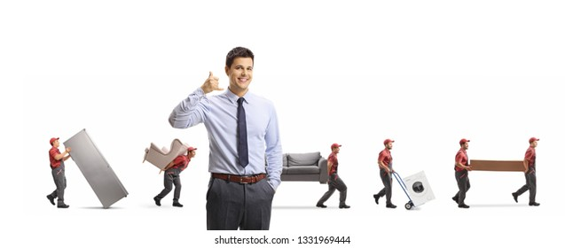 Manager of a removal company gesturing call us sign and workers carrying furniture and appliences isolated on white background