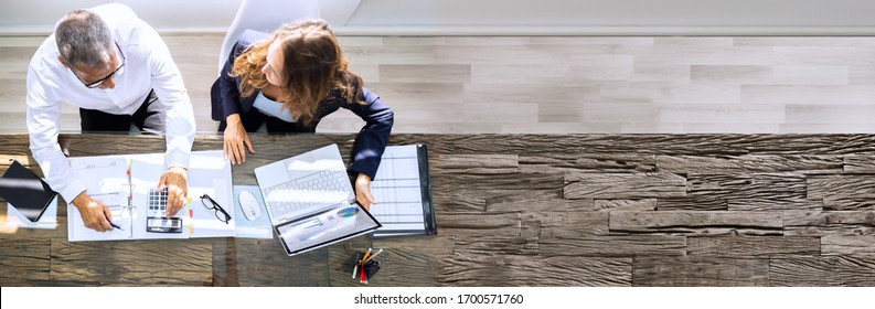 Manager And Senior Accountant Using Laptop In Office