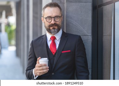 Manager senior man in business suit holding cup of coffee and laptop notebook. business lifestyle in coffee time at morning daylight.man feeling fresh and happy with confident of success.