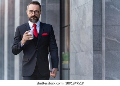 Manager senior man in business suit holding cup of coffee and laptop notebook. business lifestyle in coffee time at morning daylight. man feeling fresh and happy with confident of success.
