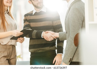 Manager shakes hands with the employee in a workplace in a modern office