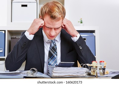 Manager sitting with burnout syndrome in his office and starring at files