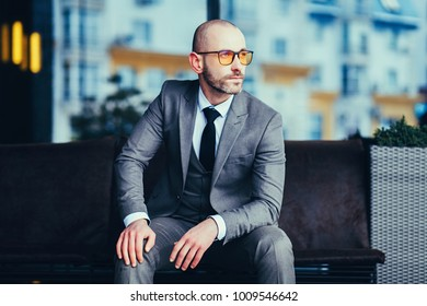 manager sitting in gray suit and glasses in office