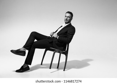 manager sitting on a chair, on a gray background, a businessman dressed in a strict stylish suit, radiates confidence, studio, free text