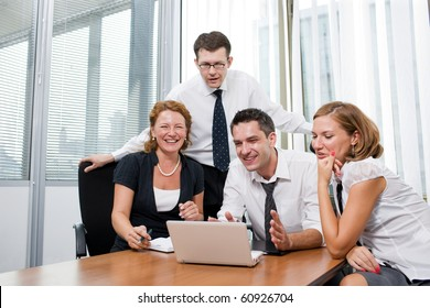 Manager sitting round table with business workers in board room Hi Res. Happy people smiling and having a meeting about burning issues.