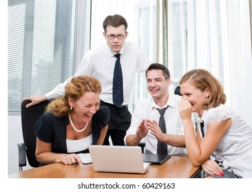 Manager spending his time with office workers during meeting in board room Hi Res. Office workers sitting round table and discussing business projects with the help of laptop computer.