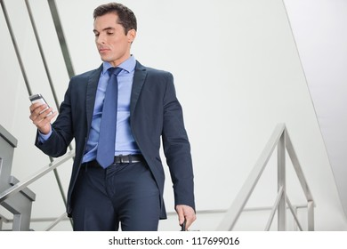 Manager in staircase looking for network coverage with his smartphone