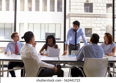Manager standing to address colleagues at a business meeting