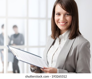 Manager with tablet on the glass wall background with people