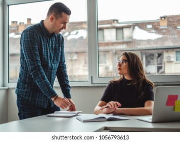 Manager talking angry to his female colleague and writing into a notebook