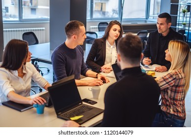 Manager talking to his staff at the office meeting while they are listening