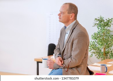 A manager thinking at his office with a desk and planning board in the background