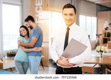 A manager in a tie poses on the camera. Near him are a guy and a girl who embrace.