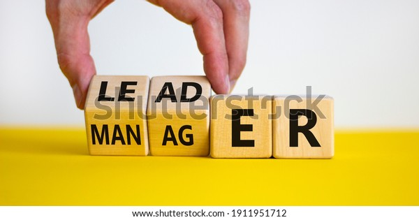 Manager versus leader symbol. Businessman flips wooden cubes and changes the word 'manager' to 'leader'. Beautiful white background, copy space. Business and manager versus leader concept.
