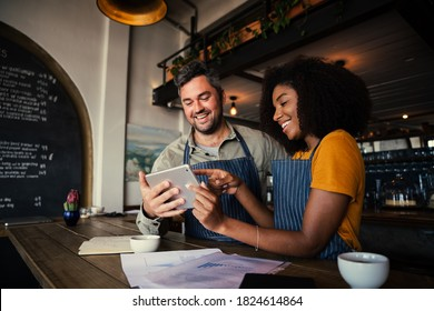 Manager and waitress laughing at designs on digital tablet standing with hot coffee in cafe