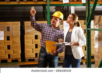 Manager and warehouse worker checking list and inventory on the shelf in storehouse.