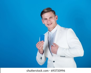 Manager wearing casual suit on blue background. Man smiling with business or bank card. Banking and saving. Businessman posing in white jacket and shirt. Fashion and information concept, copy space