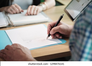 Manager at work as financial consultant talking to elderly people. Senior man meeting health insurance broker or retirement plan agent for signature on agreement