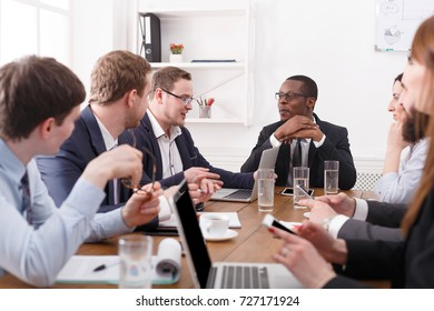 Manager with workers meeting, successful multiethnic company with black male boss. Office discussion, communication with partners at the desk