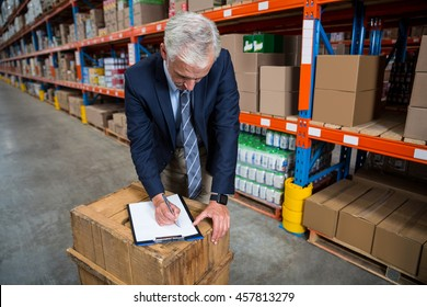 Manager writing on his clipboard in a warehouse