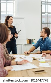 Manageress or team leader in a meeting with the young people in her business team as they sit grouped around an office table