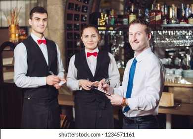Manager's briefing with the waiters. Restaurant manager and his staff.