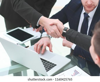 Manager's and client's handshakes over the Desk in the Bank's office