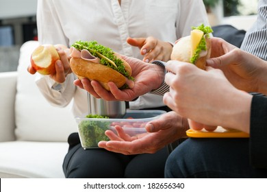 Managers discussing during lunch in office interior