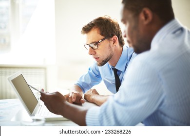 Managers discussing something on laptop