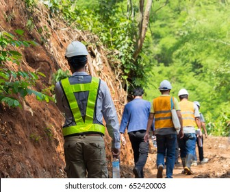 the managers and the foreman walk to the work site that is in the forest