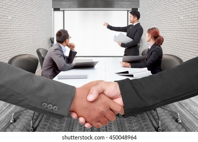 Managers handshake with business man writing and explaining something to colleagues at conference table