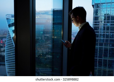 Managing director dressed in elegant clothes using mobile phone while resting after late briefing in the nighttime, young smart male entrepreneur read text message on cell telephone during work break