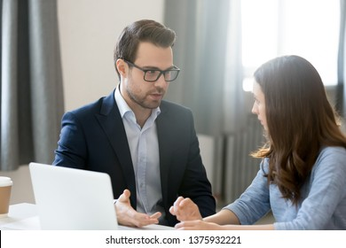 Managing director in suit talk with company client sitting at desk having business meeting negotiate solve issue, associates working together on task new startup idea, teamwork help or synergy concept