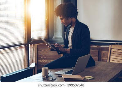 Managing his timetable. Side view of young handsome African man using his digital tablet while sitting on table at his working place