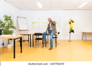 Managing partner sitting on the planning desk with a whiteboard and planning sheets on the wall behind him. A  hat stand with safety gear and several workplaces in the brightly lit, yet sparce room
