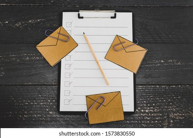 managing your inbox and business schedule conceptual still-life, email envelope icons  scattered on top of to do list on clipboard