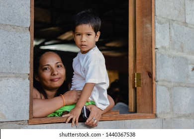 Managua, Nicaragua - June 15, 2019: A Nicaraguan woman holds her child as he sits in the window of a barrio church. Happy mother and son enjoy a visit from American missionaries.