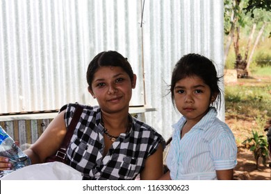Managua, Nicaragua - May 11, 2017: A mother and her daughter wait patiently to see an American missionary doctor and receive food from a missionary team at their church.