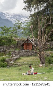Manali / India - 06 23 2014: A Indian man doing handicraft on a lawn in a small mountain village